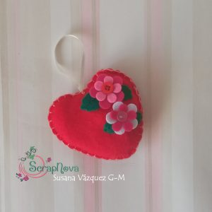 Corazón cosido tonos rosas y rojos con flores de decoración.